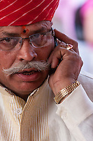 Jaipur, Rajasthan, India.  Hindu Priest Talking on Cell Phone.  He has a bindi between his eyebrows, representing the third eye or spiritual sight that Hindus seek.  It is also said to protect against demons or bad luck.
