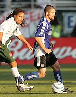 25 June 2005:   Wade Barrett of Earthquakes dribbles the ball away from Cobi Jones of LA Galaxy at Spartan Stadium in San Jose, California.   Earthquakes defeated LA Galaxy, 3-0.  Mandatory Credit: Michael Pimentel / ISI