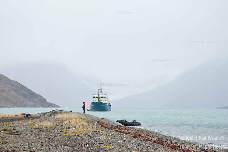 A man stands guard over the Zodiacs in Eastern Greenland. In the background the Arctic exploration ship the Akademik Shokakskiy.