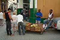 People buying fruit from a market stall on Obispo Street, Havana, Cuba.