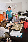 Two middle aged men, one young man and two young women of various ages look at models for landscape design and discuss project in university classroom