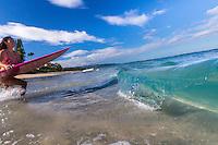 A local surfer girl runs into the ocean for a surf session at Laniakea Beach, O'ahu.