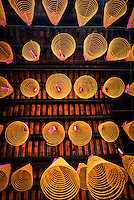 """Conical incense coils hanging on wires below the roof at Chua Thien Hau Temple in Cho Lon, Ho Chi Minh City, Vietnam.<br /> <br />  Thien Hau Pagoda. Cholon, Ho Chi Minh City, Saigon<br /> Chùa Bà Thiên Hậu is a Chinese style temple located on Nguyễn Trãi Street in the Cho Lon, District 5 of Ho Chi Minh City, Vietnam. It is dedicated to Thiên Hậu, the Lady of the Sea, who is also known as """"Mazu""""."""