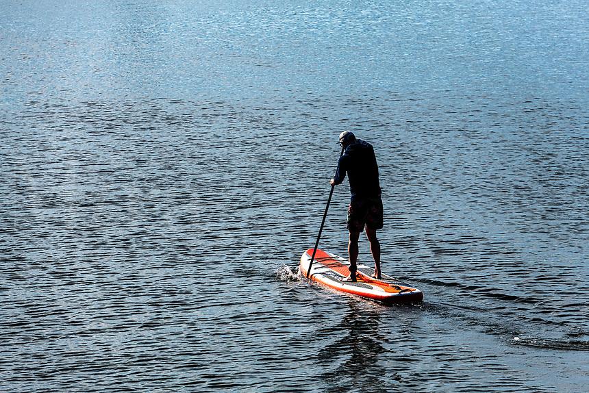 Man boarding on paddleboard, Cape Cod, Massachusetts, USA.