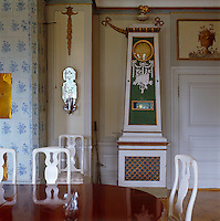 An unusual hand-painted grandfather clock in a corner of this dining room