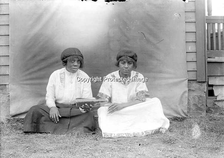 GIRLFRIENDS. These young women appear together in at least three Johnson photographs. Like the previous picture, this image is ambiguous--one friend pretends to pour a drink for the other, but the bottle is capped<br /> <br /> Photographs taken on black and white glass negatives by African American photographer(s) John Johnson and Earl McWilliams from 1910 to 1925 in Lincoln, Nebraska. Douglas Keister has 280 5x7 glass negatives taken by these photographers. Larger scans available on request.