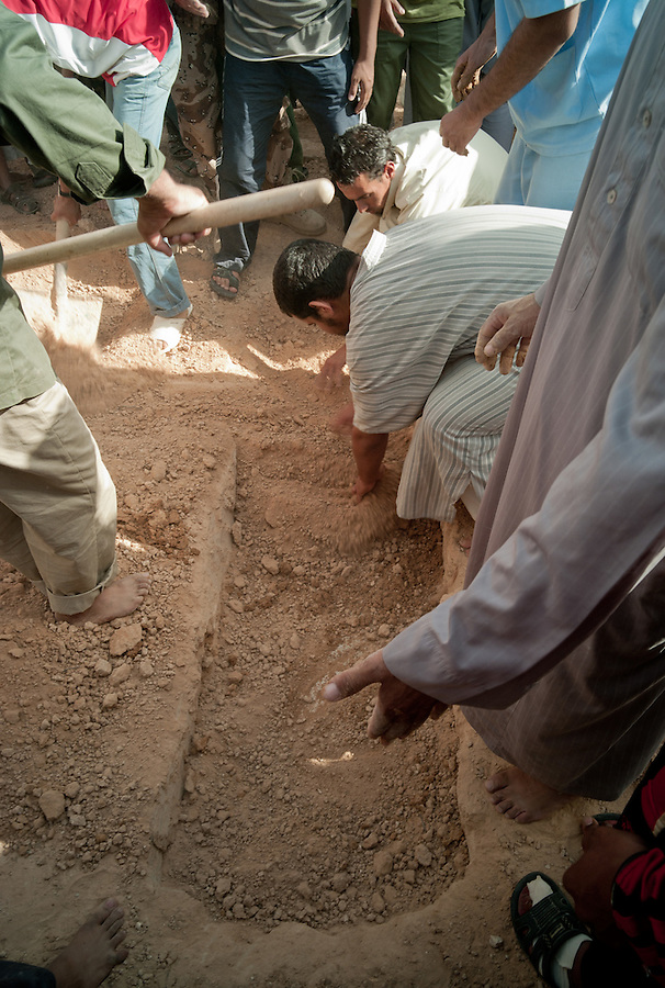 Casket is covered with earth during funeral ceremony in Zintan, Libya