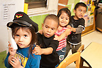 Education Preschool pretend play line up of group of children leader in dressup hat using toy telephone other children following hands on shoulders in line.