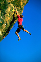 A rock climber hangs perilously by two hands from Endless Bumper in Marin County, California with blue sky in the background.<br />