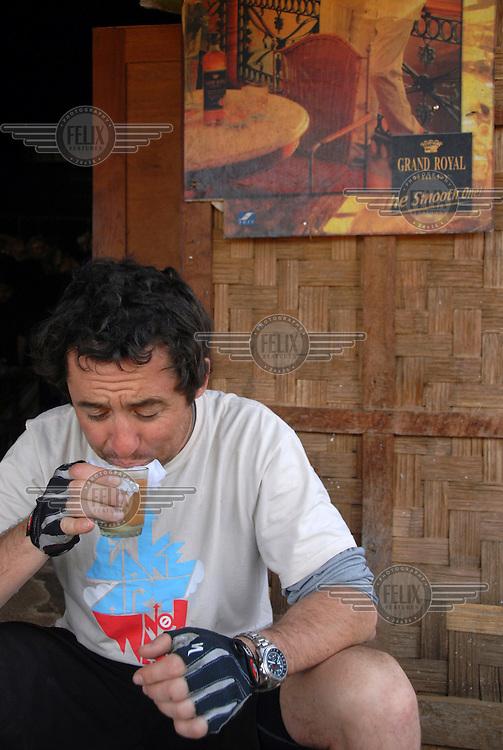 Porter enjoys a tea-break in a typical roadside Burmese tea-shop between Kalaw and Ywar Ngan. In December 2007, writer Porter Fox and his friend A'yen embarked on an ambitious cycling trip across Burma.