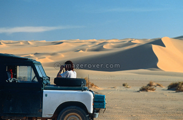 Africa, Algeria, Sahara Desert. Traveller, undertaking a sahara trip with his Series 2a Land Rover, taking a navigation stop in the scenic setting of the Sahara Desert to read the maps. --- No releases available. Automotive trademarks are the property of the trademark holder, authorization may be needed for some uses.