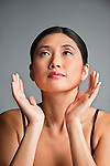 Young Asian woman framing her face with her hands