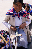 Cusco, Peru. Woman using a foot loom to weave traditional strap belts.