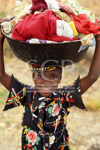 Bangweulu, Zambia. Smiling young girl in a black and multi coloured top carrying washing in a bowl on her head; Chambeshi River.