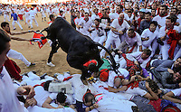 A fighting cow leaps over bull runners in the Plaza de Toros following the sixth Running after the sixth San Fermin Festival bull run, on July 12, 2012, in Pamplona, northern Spain. The festival is a symbol of Spanish culture that attracts thousands of tourists to watch the bull runs despite heavy condemnation from animal rights groups. (C) Pedro ARMESTRE