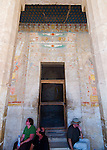 Luxor, Egypt -- Tourists rest on convenient steps, taking shelter from the day's sun and heat under a colorful night sky and the protective wings of Nekhbet, the vulture God of protection (over the door). © Rick Collier / RickCollier.com