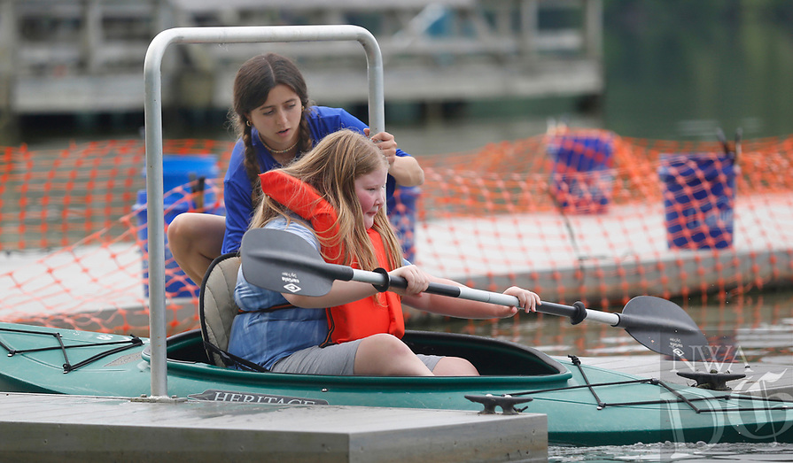 Counselor Sadie Barlow helps launch Lily Abplanalp, 10, Tuesday, June 8, 2021, in her kayak during the city of Fayetteville Parks and Recreation Outdoor Adventure Be Active summer camp at Lake Fayetteville. The week long morning camp offers activities that include disc golf, climbing, mountain biking, kayaking and others. Check out nwaonline.com/210609Daily/ and nwadg.com/photos for a photo gallery.<br /> (NWA Democrat-Gazette/David Gottschalk)