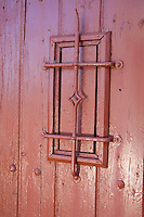 A detail of a red painted door with wrought iron grille