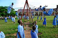 TANZANIA Bukoba, children at swing of playground in school / TANSANIA Bukoba, Kinder spielen auf dem Spielplatz einer Schule, Schaukel