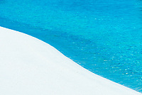 An intimate look at the white sand, lines and blue waters of the ocean shore.