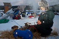 Veterinarian Jennifer Bando writes down information in Sebastian Schnuelle dog book at the village checkpoint of Ruby in Interior Alaska during the 2010 Iditarod