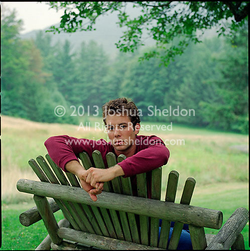 Man, sitting in adirondack chair looking over the back at camera<br />