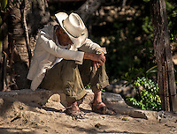 Urban Street Photograph of a Mexican man taking a siesta in the hot Mexican sun. The contrasty lighting and long shadows of the day combined with the pose of this man sitting down in a dusty  street with his hat shielding him from the bright burning sunlight reminded  me a scene right out of  a Mexican movie.