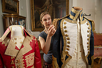 BNPS.co.uk (01202) 558833<br /> Pic: ZacharyCulpin/BNPS<br /> <br /> Pictured: Artist Stephanie Smart with the incredible paper outfits. (From left) a coat inspired by Napoleon and an early 19th century British  naval uniform.<br /> <br /> A textile artist has unveiled a collection of remarkable Regency outfits she has painstakingly made out of paper.<br /> <br /> Stephanie Smart has produced 11 life-sized outfits including a red frockcoat modelled on the style of Napoleon.<br /> <br /> Others depict walking dresses, naval uniforms and spencer jackets from the Regency era. (1795-1837)<br /> <br /> Her creations are on display as part of an exhibition titled The Regency Wardrobe at Firlie Place in East Sussex.