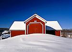 Snow drifts around a historic high bridgeway type barn near Treadwell, Delaware County, New York