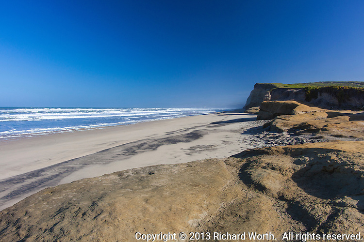 The bluffs at Pomponio Beach face clear blue skies and gently rolling waves.