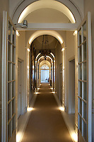 A long arched corridor is illuminated with concealed floor and ceiling lights