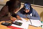 Education High School mathematics or science two female students working together calculator nearby