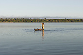 Xingu Indigenous Park, Mato Grosso State, Brazil. Aldeia Kamaiura; a woman with her children in a dugout canoe on Lake Ipaivu.