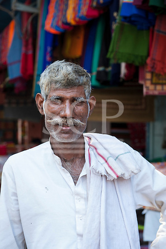 Rajasthan, India. Sawai Madhopur. Grey-haired shawl salesman in a white shirt with moustache.