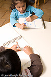 Preschool Headstart 3-5 year olds art activity girl and boy drawing with markers vertical both using left hand