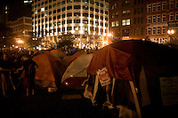 OccupyBoston protesters wait for a planned police action at their second encampment at Rose F. Kennedy Greenway a block from Dewey Square, in downtown Boston, Massachusetts, USA.  The police and city officials warned protesters that they would be forceably removed from the site by midnight.  At about 1:30am police moved into the park, arrested approximately 100 protesters, and cleared the park of all tents and other protest materials.  The protesters are part of OccupyBoston, which is part of the OccupyWallStreet movement, expressing discontent with the socioeconomic situation of the 99% of the US population who are not wealthy.  Protestors have been camping in Dewey Square since Sept. 30, 2011. Gradually, larger organizations, including major labor unions, have expressed their support for the OccupyBoston effort.