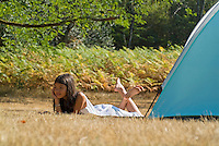 Young Asian girl lying down beside a camping tent in the Landes Forest, Aquitaine, France.