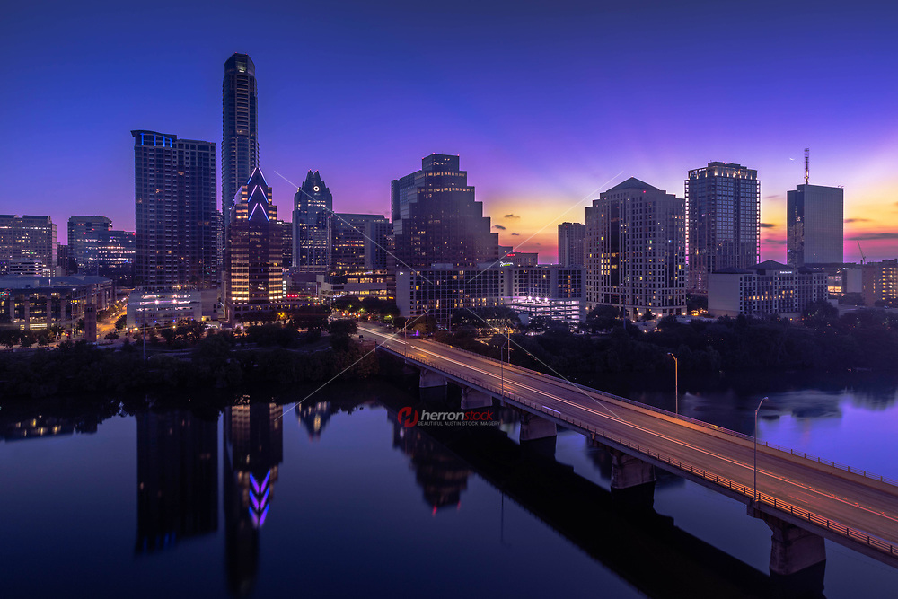 A high-rise building boom is reshaping Austin's skyline as shown in this image a beautiful morning sunrise captures the Austin Cityscape as the sun pops up above the horizon and illuminates a hallow around the city's ever booming skyline in downtown Austin, Texas.