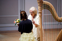USA International Harp Competition Vice President Linda Wood Rollo gives flowers to performer Annette Lee during the Stars of Tomorrow Concert at the 11th USA International Harp Competition at Indiana University in Bloomington, Indiana on Thursday, July 11, 2019. (Photo by James Brosher)
