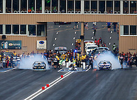 Jul. 18, 2014; Morrison, CO, USA; NHRA pro stock driver Jason Line (right) and Chris McGaha do side by side burnouts during qualifying for the Mile High Nationals at Bandimere Speedway. Mandatory Credit: Mark J. Rebilas-
