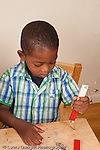 3 year old boy using bar magnet to pick up metal objects vertical