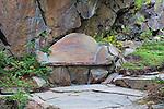 Stone bench marks a viewpoint rest stop along cliffside stone path through alpine botanical garden.  Ohme Gardens, Wenatchee, Chelan County, Washington, USA.
