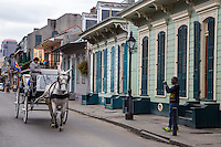 French Quarter, New Orleans, Louisiana.  Mule-drawn carriage Passing Two Shotgun Houses, Bourbon Street.