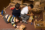 Education preschoool children ages 3-5 block area group of three boys playing separately horizontal