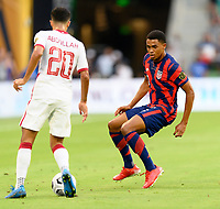 AUSTIN, TX - JULY 29: Reggie Cannon #2 of the United States defends against Abdullah Al Ahrak #20 of Qatar during a game between Qatar and USMNT at Q2 Stadium on July 29, 2021 in Austin, Texas.