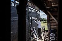 Nathan Mwambada adjusting the names on the jockey borad during the races at Ngong Racecourse in Nairobi, Kenya March 17, 2013 Photo: Brendan Bannon