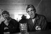 - Delta del Danubio, Tulcea. Due lavoratori bevono in un bar nella zona della città vecchia...- Danube Delta Area, Tulcea. Two workwrs drink some withe wine in a beer mug.in a cafe placed in the old part of the town...