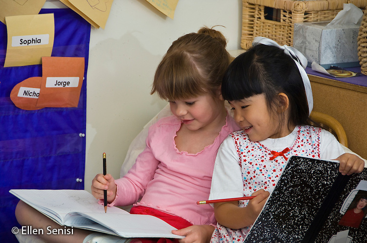 MR / College Park, Maryland.Center for Young Children, laboratory school within the College of Education at the University of Maryland. Full day developmental program of early childhood education for children of faculty, staff, and students at the university..Two girls (5) sit on chair together writing in their writing journals and talking..MR: Tro11 Bai3.© Ellen B. Senisi