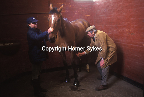 Badminton, Gloucestershire. 1995<br /> Brian Higham a long serving Stud Groom at The Duke of Beaufort Badminton House estate. Seen here with stable girl 'flaming' a horse; burning down the very tiny horse hairs that are out of place, so the horse's coat looks absolutely perfect.