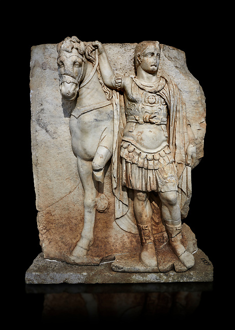 Roman Sebasteion relief sculpture of  an Imperial prince as Diokouros, Aphrodisias Museum, Aphrodisias, Turkey.   Against a black background.<br /> <br /> An imperial youth wearing a military cloak and cuirass of a commander holds the reins of hios horse. This panel is next to a Claudius panel so is probably of Britanicus or Nero the emperors son and intended successor